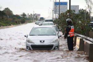 رجل أمن يزاول عمله وسط الأمطار و السيول الغزيرة في الدار البيضاء و يثير الجدل في مواقع التواصل